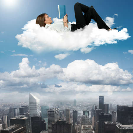 unbend: Businesswoman reading book on a cloud Stock Photo