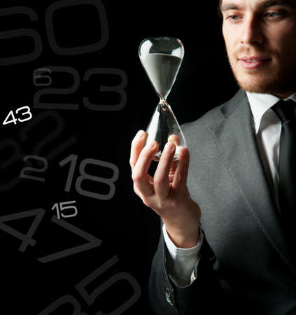 Businessman holding a hourglass with a girl inside photo