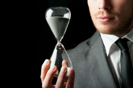 woman with clock: Businessman holding a hourglass with a girl inside Stock Photo