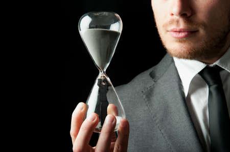 woman clock: De negocios que sostiene un reloj de arena con una chica en el interior