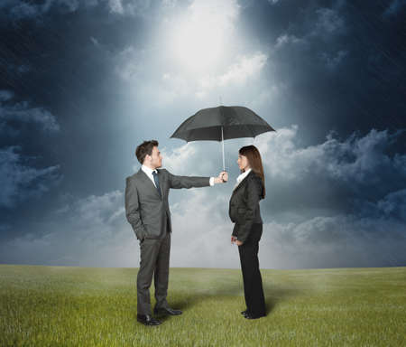 Businessman protect a woman with umbrella. photo