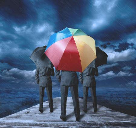uomo sotto la pioggia: Imprenditore pensa positivamente durante la tempesta Archivio Fotografico