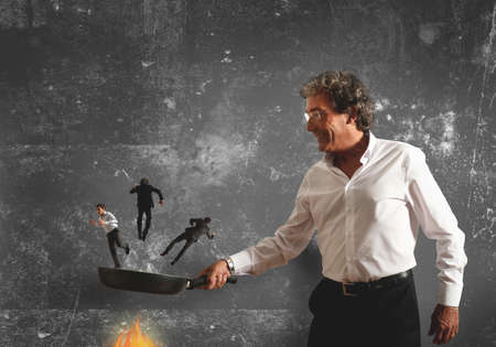 sear: Concept of business man that burns in the pan the competitor Stock Photo