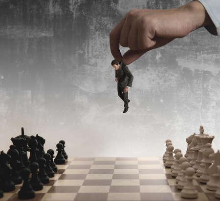 tablero de ajedrez: Un jefe utiliza como un pe�n de un hombre de negocios en un tablero de ajedrez Foto de archivo
