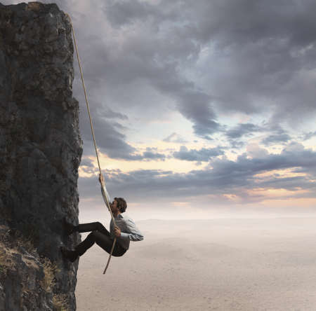 Businessman climbs the mountain. Concept of professional success