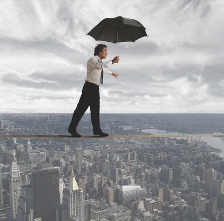 risky job: Businessman trying to keep balance between the difficulties