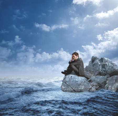 Zakenman in een crisis op de rotsen