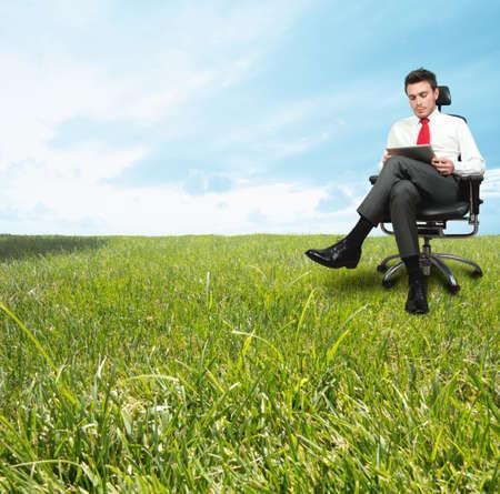 緑の野原で、リラックスした日を楽しんでいる実業家