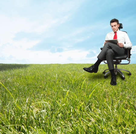 A businessman enjoying a relaxing day in a green field