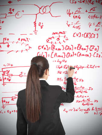 Businesswoman drawing formula in a whiteboard photo