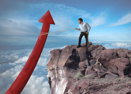 tries: Businessman tries to raise the statistics over a mountain Stock Photo