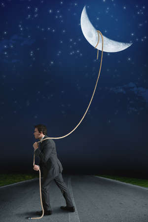 volition: Concept of businessman who obtains the moon with determination