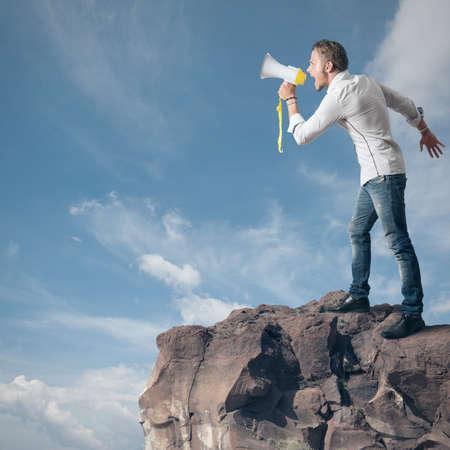 comunicarse: Muchacho que grita en el megáfono en la montaña Foto de archivo