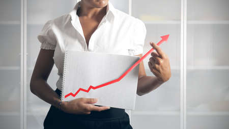 helps: Businesswoman helps statistics trend to growth Stock Photo