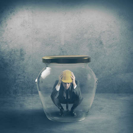 trapped: Scared businessman in a jar