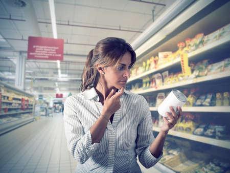 Garota insegura sobre a autenticidade do produto no supermercado Foto de archivo