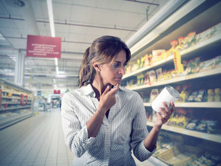 Girl unsure about the authenticity of the product at supermarket photo