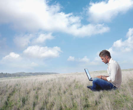 computer worker: Boy works in a field with laptop