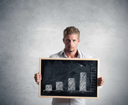 Businessman show positive trend in a blackboard Stock Photo - 15948708