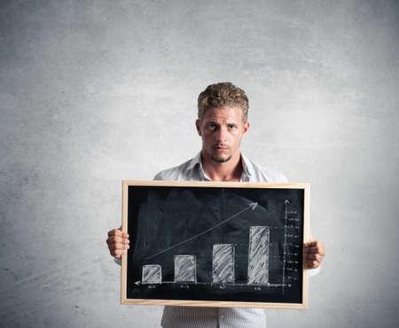 Businessman show positive trend in a blackboard Stock Photo - 15948708