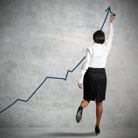 increment: Businesswoman drawing statistics in a wall