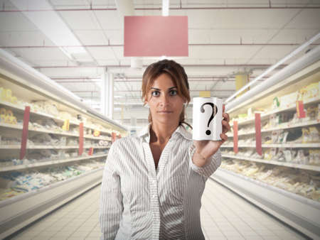 supermarket shopping: Girl at supermarket that show an unknow product