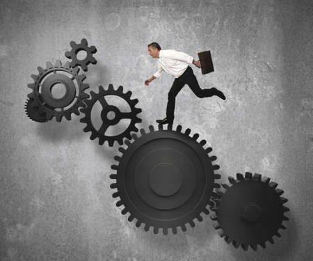 business stress: Businessman jump on gear system