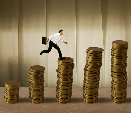 market trends: Jumping businessman in a stack of money Stock Photo