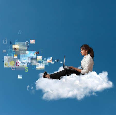 Conceito de multimídia com uma mulher de negócios sobre uma nuvem, com um laptop