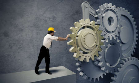 Businessman turning a gear business system photo