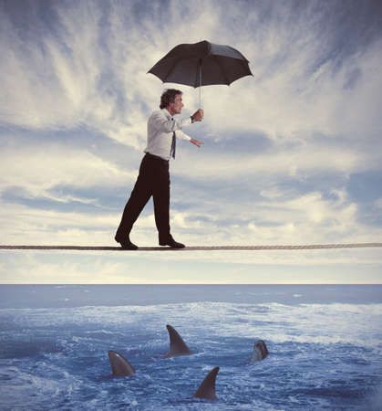risky job: Concept of insurance with businessman on the rope