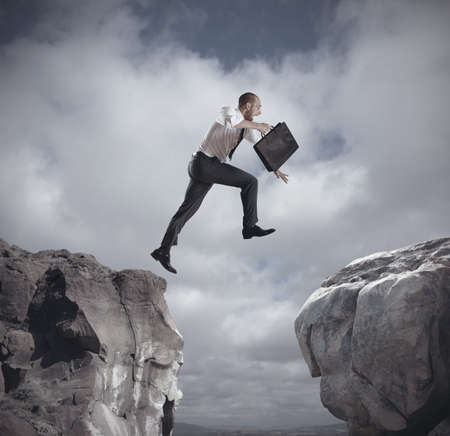 risky job: Businessman jumping over the mountains  concept of ambition in business Stock Photo