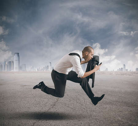 run way: Businessman running with mobile phone in hand Stock Photo