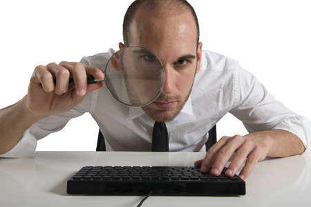 Businessman  looks on the computer with a magnifying glass Stock Photo - 17455038