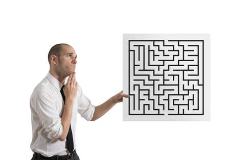 complication: Businessman looking for a solution of a maze Stock Photo