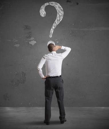 dudas: Confundido hombre de negocios mirando signo de interrogación en la pared