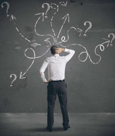 uncertain: Empresario mirando flechas apuntando en direcciones diferentes