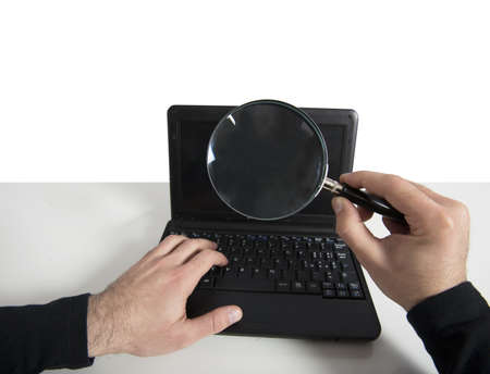 Hacker looking for a password in a laptop with lens Stock Photo - 17905735