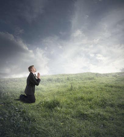 orando: Hombre de negocios est� orando para resolver la crisis financiera Foto de archivo
