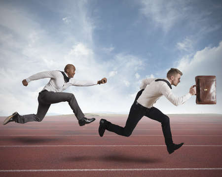 triunfador: Conceot de la competencia con dos hombre de negocios corriendo en una pista