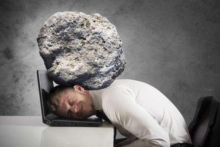 Concepto de estrés con el empresario con una piedra en la cabeza Foto de archivo