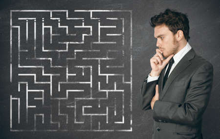 Businessman seek the solution of a complex maze photo
