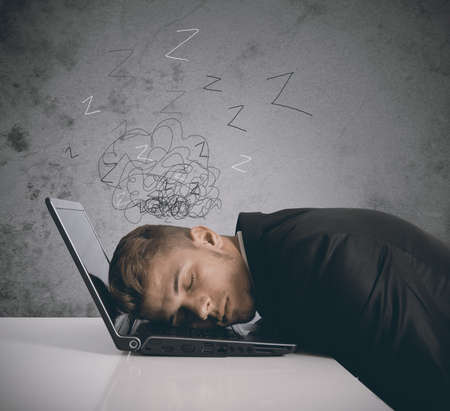 Tired businessman sleeping on a laptop photo