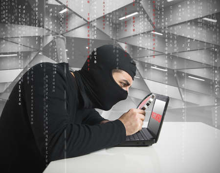 online privacy: Hacker look for password in a laptop