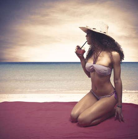 women in bikini: Beautiful girl drinking cocktail on the beach Stock Photo
