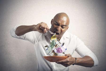 avid: Concept of businessman that eats the money