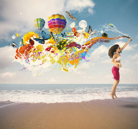 elation: Summer color explosion with jumping girl at the beach Stock Photo