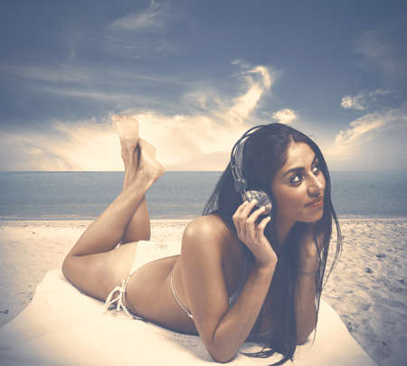 Young girl listens to music at the beach Stock Photo - 19609315