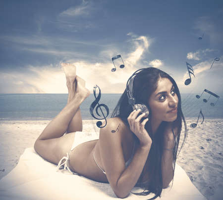 sexy headphones: Young girl listens to music at the beach