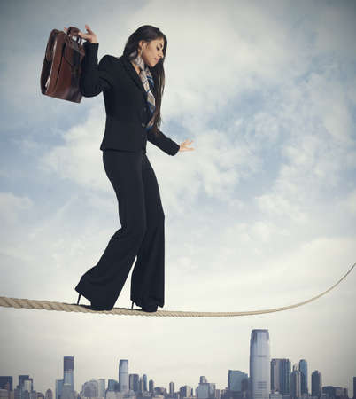 Concept of risk in business with businesswoman on the rope photo